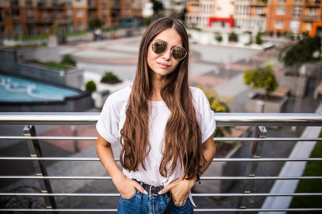 ヨーロッパの都市の橋の上のかわいい若い女性の屋外のポートレート。