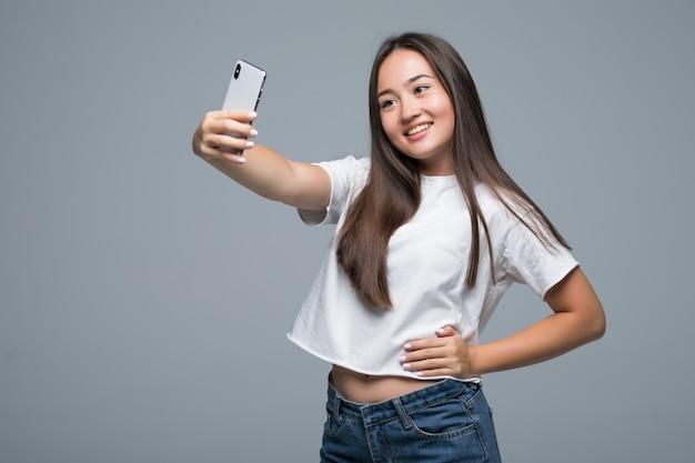 Улыбается молодая азиатская женщина, принимая селфи с мобильным телефоном на изолированных сером фоне стены