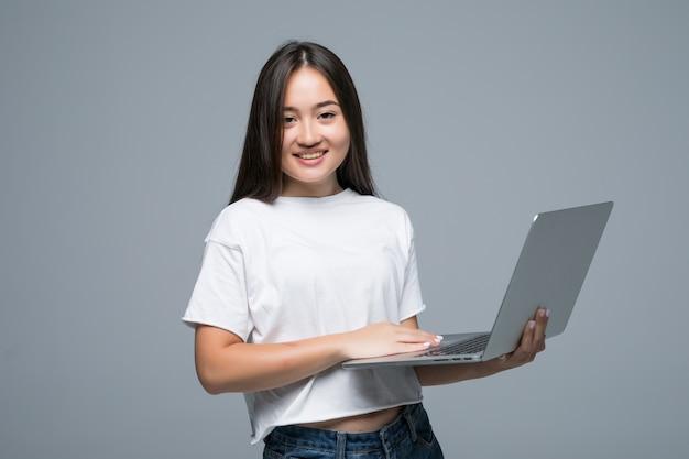 Азиатская женщина, держащая портативный компьютер, глядя на камеру на сером фоне