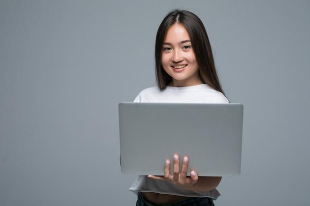 灰色の背景の上にカメラを見ながらラップトップコンピューターを保持しているアジアの女性