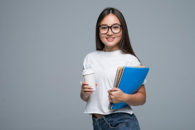 ノートブックと灰色の背景に対して隔離された立っている手に行くコーヒーと若いアジアの女の子