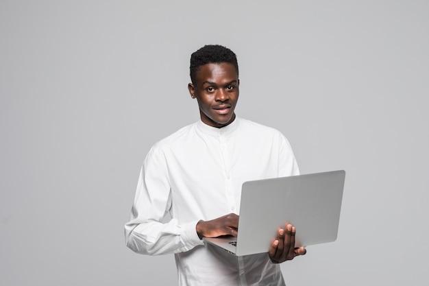 ラップトップコンピューターを使用して白い背景に分離されて立っている幸せな若いアフリカ人。
