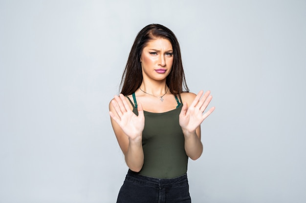 Портрет молодой привлекательной женщины показывая знак стопа при изолированная ладонь