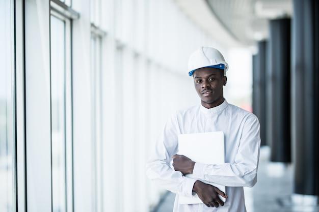 Инженер в каске стоит с ноутбуком в офисе возле панорамного окна
