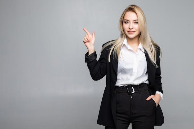 Молодая бизнес-леди указывая пальцем в сторону на изолированной серой стене