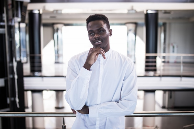 眼鏡でハンサムな青年実業家がオフィスホールに立っている間考えています。