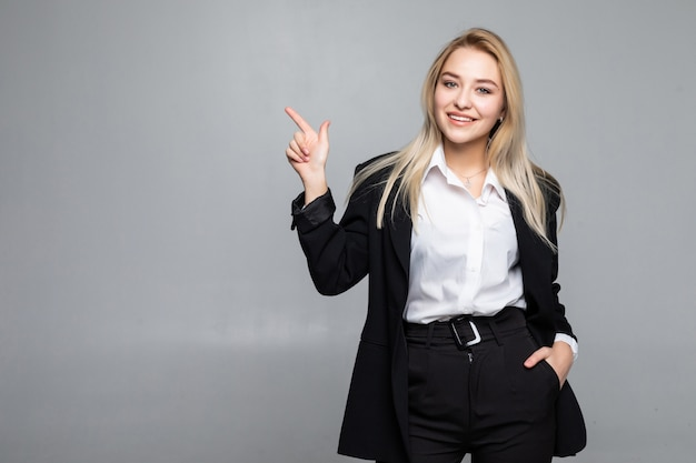 孤立した灰色の壁の側に指を指す若いビジネス女性