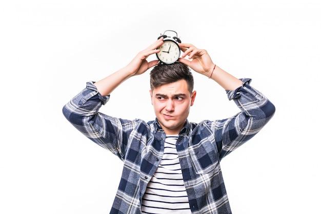 若い男子生徒が彼の頭に黒い髪の目覚まし時計を保持します。