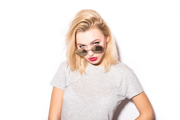 白い壁に分離された眼鏡をかけている美しい女性