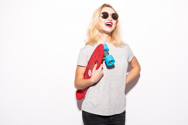 Женщина в блестящих солнечных очках со скейтбордом в руках