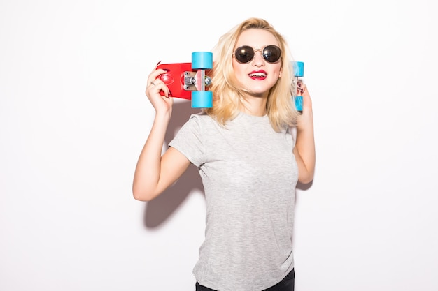 若い女性は彼女の頭の後ろに赤いスケートボードを保持します