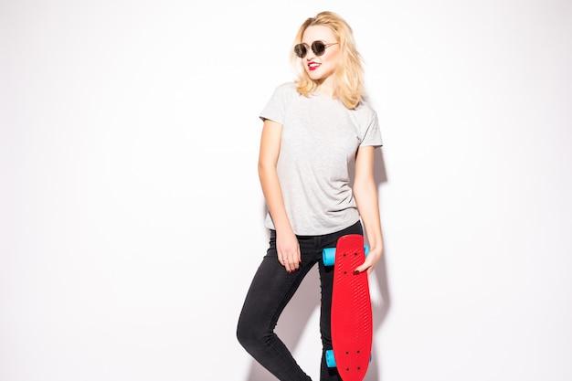 Красивая девушка-скейтер в серой футболке стоит перед белой стеной
