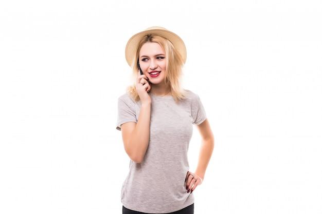 Улыбается женщина, используя новый мобильный телефон в черном корпусе