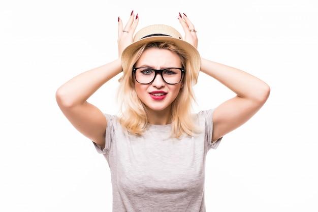 Блондинка держит ее лицо в изумлении, изолированных на белой стене