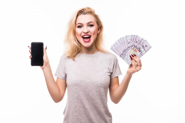 Взволнованная молодая женщина с большой улыбкой держит веер долларовых купюр