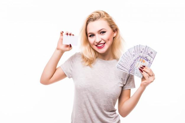 お金と白い壁に分離された白いクレジットカードのファンを保持している女性