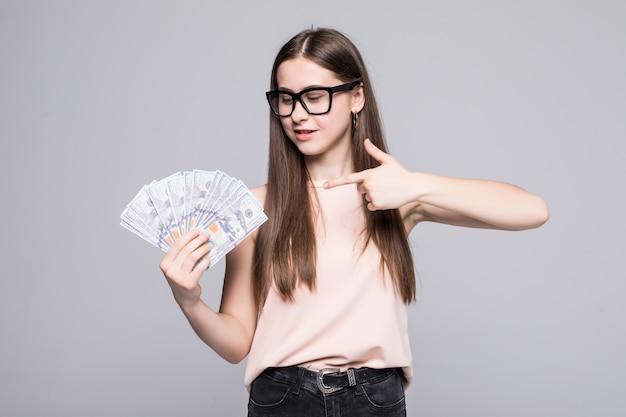 Молодая женщина, показывая на деньги, доллар, изолированные на серую стену