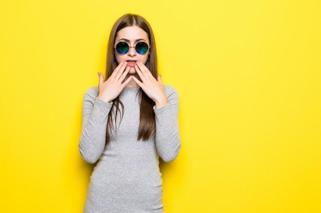 立っている興奮して叫んでいる若い女性黄色の壁の上に孤立