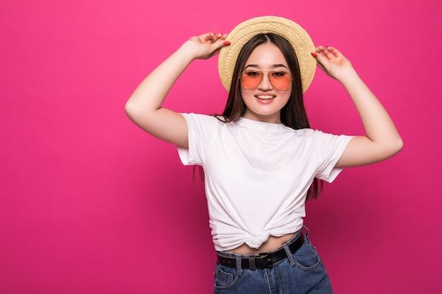 Портрет жизнерадостной азиатской женщины над розовой стеной