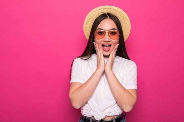 ピンクの壁に幸せで楽しいアジアの女性を考えてください。