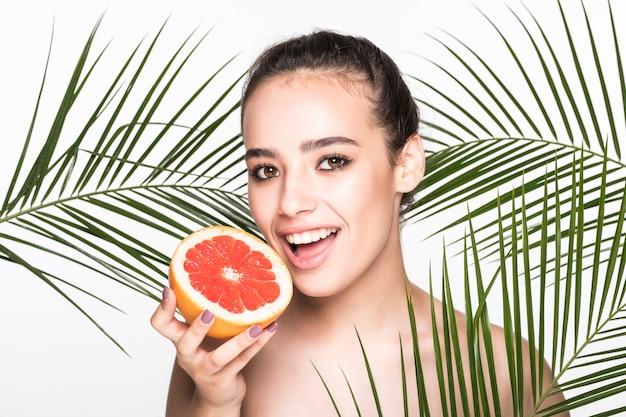 Молодая женщина с идеальной кожей держит цитрусовые в руке в окружении пальмовых листьев, изолированных на белой стене
