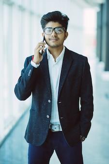 近代的なオフィスに携帯電話で話している若いハンサムなインドのビジネスマン