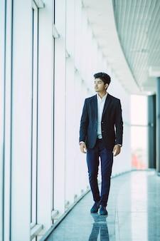 朝のオフィスに歩いて若いアジアインドのビジネスマン