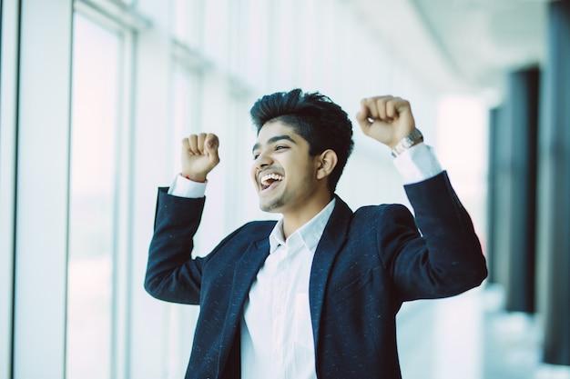 オフィスの窓の近くの成功勝利ジェスチャーを表現するスーツのインドのビジネスマン