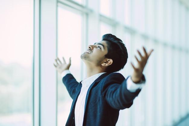 素晴らしいニュースを祝う近代的なオフィスで幸せなハンサムなインドのビジネスマン