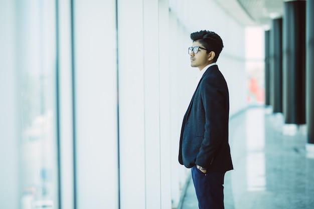 Портрет индийского делового человека, улыбаясь в современном офисе