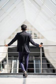 近代的なオフィスのビジネスマンの背面図