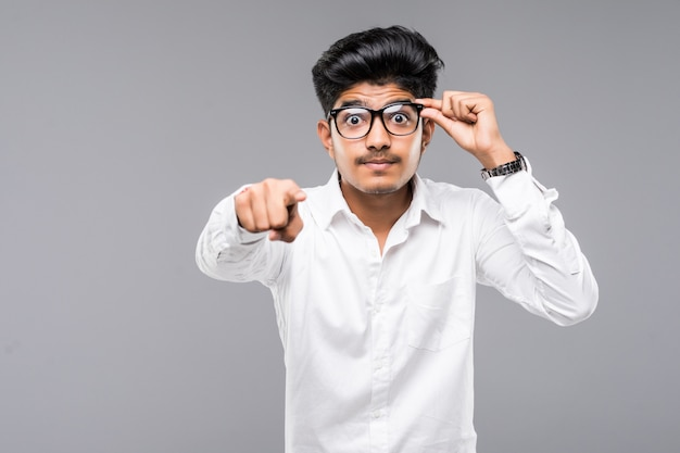 インドのビジネスマンが灰色の壁にあなたを指す