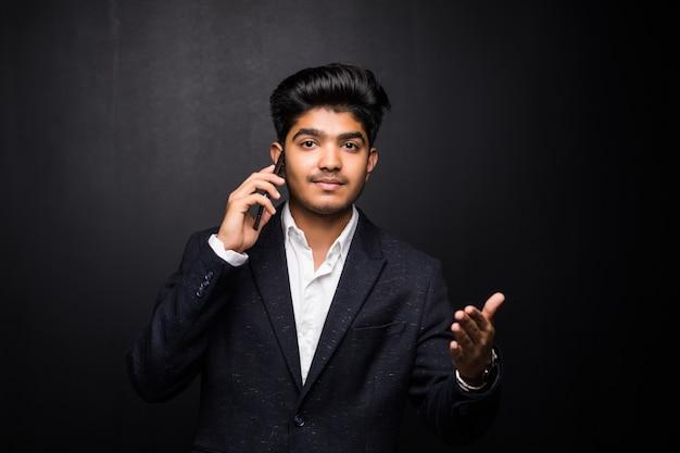 Индийский деловой человек разговаривает по телефону на черной стене