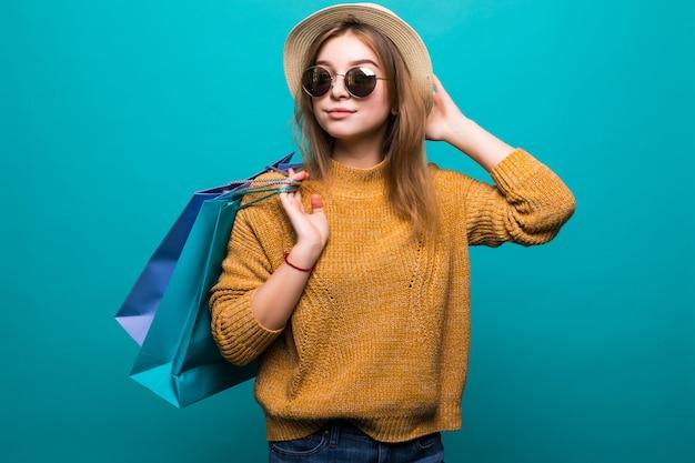 Молодая предназначенная для подростков женщина в солнечных очках и шляпе держа хозяйственные сумки в ее руках чувствуя так счастье изолированное на зеленой стене