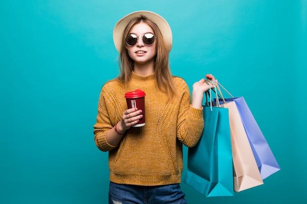 移動するコーヒーを保持していると水色の壁に笑みを浮かべて買い物袋を保持している若い女性