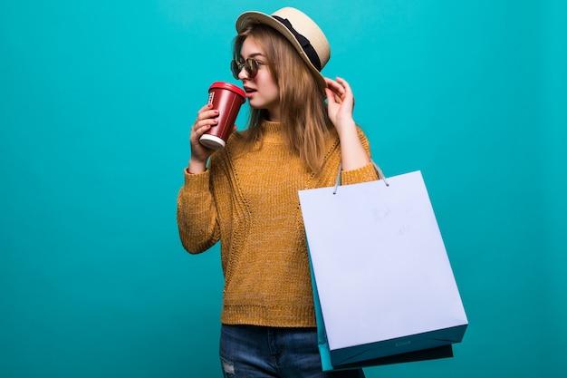 買い物袋と新鮮なコーヒーの紙コップを持つ魅力的な若い女性の肖像画