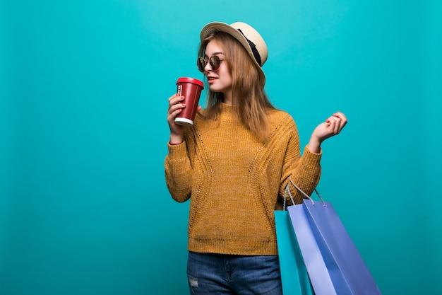 Портрет привлекательной молодой женщины с хозяйственными сумками и бумажным стаканчиком свежего кофе