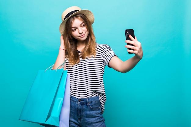 Молодая женщина делает селфи на вашем смартфоне, сидя с цветными сумками для покупок