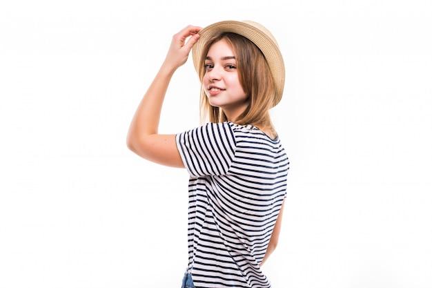 Молодая милая женщина с соломенной шляпой изолированная на белой стене