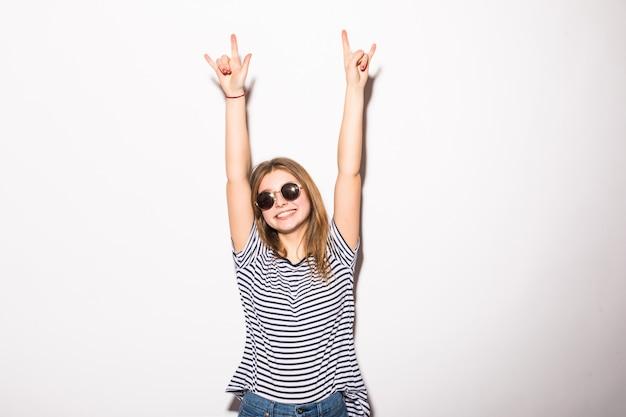 Молодая женщина с очками, давая знак рок-н-ролл, изолированные на белой стене