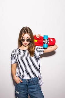 白い壁の上に立っている間スケートボードでポーズのサングラスの若い女性の肖像画