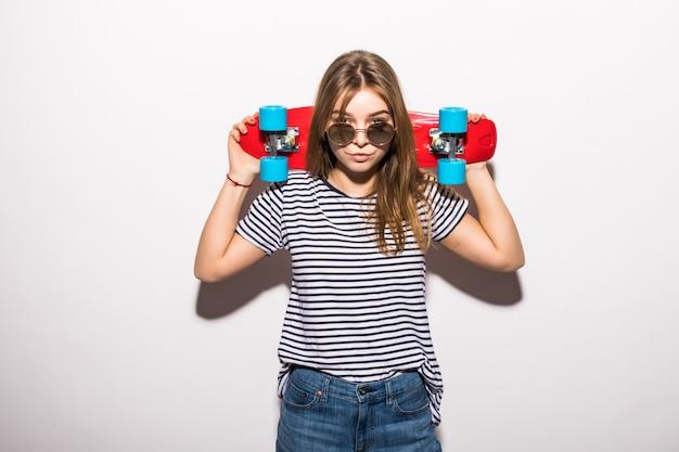 Портрет молодой женщины в солнцезащитных очках позирует с скейтборд, стоя над белой стеной