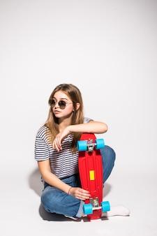Портрет девушки подростка в солнечных очках представляя с скейтбордом пока стоящ над белой стеной