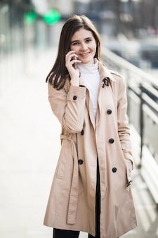 明るい茶色のコートウォーキングと外で携帯電話で話しているファッション女性