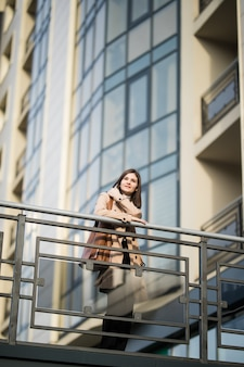 サングラスでカジュアルな服を着たブルネットの女性モデルは橋の上にとどまる