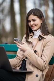 Улыбающаяся нежная модельная девушка работает на ноутбуке и телефоне на улице в парке
