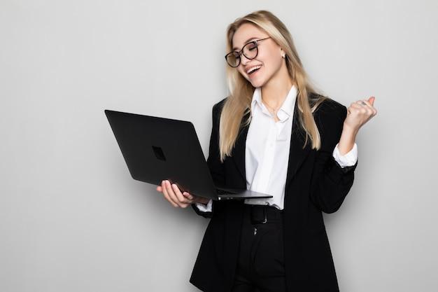 ラップトップを使用して作業している美しい若い女性は腕を上げ、笑みを浮かべて、白い壁を越えて成功するために叫んで勝者ジェスチャーをして非常に幸せで興奮しています。お祝いのコンセプトです。