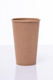 白で隔離される開いた紙茶色のコーヒーカップ