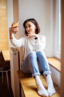 Очаровательная женщина, сидя на подоконнике в синих джинсах с телефоном, делая селф