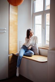 Нежная молодая женщина сидит на широком подоконнике в синих джинсах и белой футболке